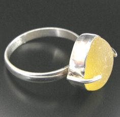 Rounded, bright golden yellow sea glass from England's North Sea is fitted into this sterling silver ring.