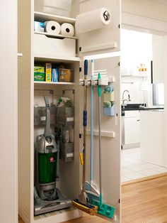 Finding a place to stow cleaning supplies can be challenging, especially if storage space is limited. Here, a narrow closet nook corrals essential supplies near the kitchen. Small bins organize bottles and brushes, and a door-mounted holder secures taller tools.