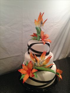 Wedding cake, bird of paradise, lilies wrapped in black ribbon- guava, mango & lilikoi tiers.  Copied another pinner for inspiration, thanks!!!
