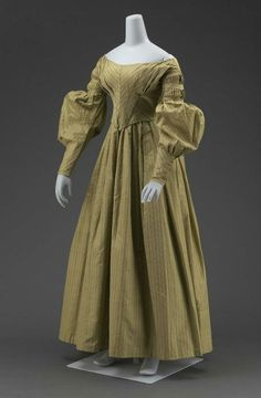 "Going away dress and matching cape, 1838 US, the Museum of Fine Arts, Boston  Newly wedded couples change into ""going away"" outfits before leaving their reception.  This tradition is fading in most places, but it's still hanging on here in the South.    Dress (a) and matching cape (b) of grayish-olive-green silk with fancy-woven stripes with lines of white; fitted bodice, pointed in front; widely flaring neck; fullness across bust in unpressed pleats; long sleeves with fine pleats"