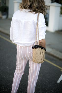 pink stripe trousers, white linen shirt, basket bag with pom poms,