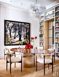 A dining area with built-in bookshelves, a unique ceiling fixture, and a brass table | archdigest.com