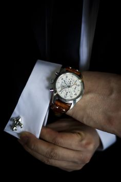 IWC [Looks like one of their pilot's watches with some sort of VERY handsome strap. . . VERY lovely indeed! Oh and the fleur de l'ile cufflinks are beautiful too.]