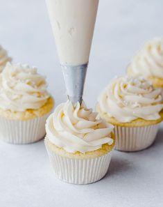 Piping vanilla frosting onto vanilla cupcakes.