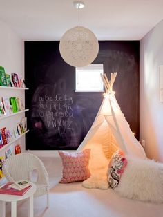 Such a neat kid's space with book ledges lining the wall, a tent with twinkle lights, and a giant chalkboard wall.