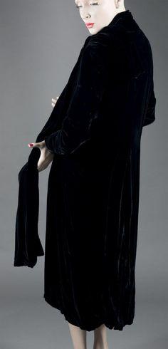 JEAN PATOU Manteau du soir en velours, vers 1930. Velours de soie noire, col-écharpe boutonné sur l'épaule, doublure satin ivoire. Griffe signature tissée rose sur satin ivoire.