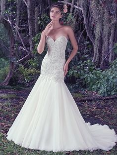 Maggie Sottero - BAXTER, Perfect for the truly romantic bride, embellished lace adorns the bodice of this Chic organza fit and flare wedding dress. Finished with a classic sweetheart neckline and covered buttons over zipper and inner corset closure.