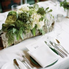 Narrow, hollowed-out logs filled with white and green florals as centerpieces // photo by: James Christianson Photographer