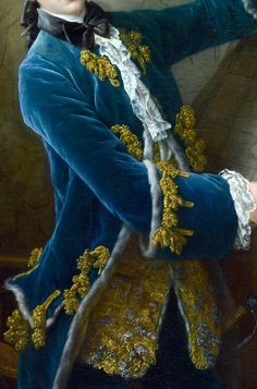 Fashion detail of gentleman's clothing c1758. Note fur-lined frockcoat of blue velvet with gold thread fly fringe embellishment to pockets and large upturned cuffs. Fur-lined waistcoat with matching gold and silver fly fringe worked front panels; delicate white lace to wrists and jabot (shirt front). Black ribbon to hair and solitaire affixed and tied in front over white cravat. https://commons.wikimedia.org/wiki/File:Comte-de-Vaudreuil-1758-par-Francois-Hubert-Drouais.jpeg