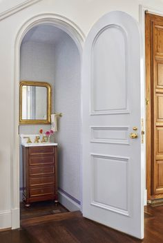 Tiny hidden powder bath under the stair. Loving that arched door Design by Collins Interiors