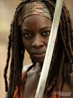 Michonne (main character) Andrea is  rescued by a katana-wielding hooded figure, who decapitates the walker. The hooded figure has two walkers shackled to her, with both of their arms and lower jaws cut off. Later the rescuer is revealed to be Michonne. Andrea and Michonne become close friends throughout the winter until they entered Woodbury. Later Michonne left Woodbury and became a key member of Rick Grimes' group. Her favored weapon is the katana.