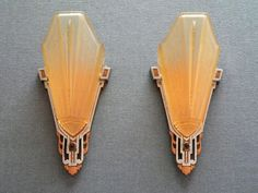 This pair of Art Deco sconces was made by the Markel Company. The light amber glass, slip shades have geometric designs. The metal backplates have been