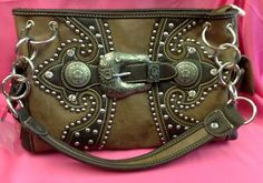 Gorgeous and soft camel-colored leather handbag with rhinestone and pewter conchos and buckle accents. Two straps. Brown trim. Made by Montana West.