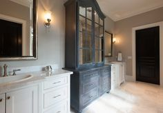 Bathroom. Bathroom boasts a dark gray distressed linen cabinet ...