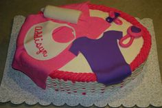 Personalized baby shower basket cake.  The blanket, onesie, rattle, pacifier, and bottle are made of fondant.