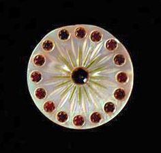 18th C. Mother of Pearl button with incised sunburst picked out in green pigment. Bordered by red stars over gold sequins. bmagic.org.uk
