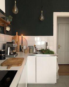 Harmonische Farben in der Küche dank Holzbrettern, Dunkelgrüner Wandfarbe, weißen Schränken und Kerze