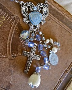 I took a pretty pale blue vintage rosary and made it into a one of a kind necklace.  The centerpiece is a silver decorative heart shaped vintage