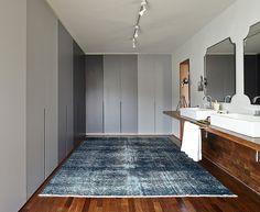No espaço criado pela arquiteta Daniela Ruiz, os armários em tons de cinza dividem o ambiente com as cubas, os espelhos e a bancada deslocadas da área interna do banheiro para o closet