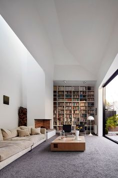 Soggiorno minimal moderno, semplice e pulito ideale per relax. Le grandi porte finestre assicurano una bellissima luce naturale. Una grande libreria completa l'ambiente