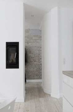 neutral flooring, exposed brick wall, black and white