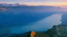 The stunning and awe-inspiring view out over Lake Brienz where travellers can take a ferry while gazing upon the red and burnt orange mountains lit up by the sunset Switzerland Tourism, Europe Train, Haul, Alpine Lake, Travel And Tourism, Travel Europe, Cool Backgrounds, Best Western, Adventure Awaits