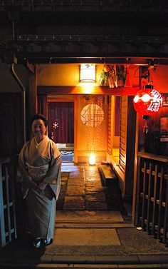 Tamakazu outside her tea house and okiya in Gion Kobu. She is the Okasan of the…