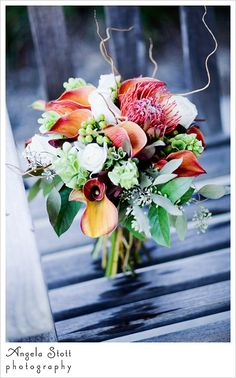 Autumn colored bridal bouquet with orange and green rustique flowers and twigs on a bench in the Norfolk Botanical Gardens, Virginia.