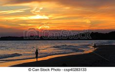 Two boys running along the beach at sunset.