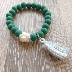 Armband van 8mm winter green hou met meerkleurig blauw kwastje en witte roos. Van JuudsBoetiek, €3,50. Te bestellen op www.juudsboetiek.nl.