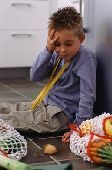 42-15334892 Boy sitting on floor in kitchen looking at broken egg