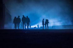 Performance im Nebel 03 – Beunruhigende Performance in Blau: Menschen nachts im Scheinwerferlicht. Hunde bellen. Der Nebel zeichnet in der Tiefe unterschiedliche Schärfen und Tonwerte. 2013, MD | © www.piqt.de | #PIQT