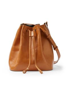 A whole lot of style meets a whole lot of utility, with this petite leather bucket bag. An easygoing aesthetic fits everything you need, while an adjustable strap slings over the shoulder or cross-body.  Drawstring closure Inner