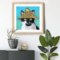 Cat in fishing hat with frog #walldecorart #gicleeprint #catprint #catart #catdecor #autism #autismawareness #wallartprint #wallart All art is created from painted textures my son with autism creates and that I use as my palette to create images.