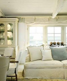 Beautiful white painted cabinet. Love the white couch and all the shades of white, cream and grey