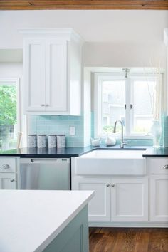 Tiffany blue kitchen features white cabinets adorned with nickel cup pulls paired with black quartz countertops and a tiffany blue subway tiled backsplash. A farmhouse sink next to a stainless steel dishwasher. Backsplash Azul, White Kitchen Backsplash, Kitchen Redo, Kitchen Tiles, Kitchen Colors, New Kitchen, Kitchen Remodel, Backsplash Ideas, Kitchen White