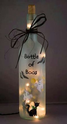 Bottle of Boos!! Halloween lighted bottle created from a recycled wine bottle which has a frosted effect . The Bottle of Boos has been created with a spooky ghost, flying bats, and (of course) a black cat. Bottle is a standard 750 ml wine bottle. A small hole was carefully drilled into the back of the lighted bottle and a 20 count set of white rice lights is used to illuminate the Halloween lighted bottle. The lighted bottle is re-corked and and tied with strands of black raffia.