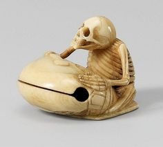 A narwhal tusk netsuke of a skeleton beating a mokugyo, by Yûgyoku. Late 19th century. The skeleton sits on a zabuton, the striker in his hand placed on top of the mokugyo in front of him. Signed Yûgyoku tô.