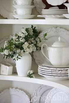 White dishes in a china cabinet.