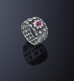 A ruby and diamond ring, by Buccellati The pierced openwork honeycomb band set to the centre with a oval ruby and circular cut diamond cluster, and decorated with similarly cut diamond accents, ring size L ½, signed 'Buccellati'. Diamond Jewelry, Gemstone Jewelry, India Jewelry, Jewellery, Smoky Quartz Ring, Unusual Jewelry, High Jewelry, Beautiful Rings, Diamond Cuts