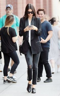 Kendall Jenner wears a tuxedo blazer with a white blouse, distressed jeans, and a mini bucket bag with oxfords