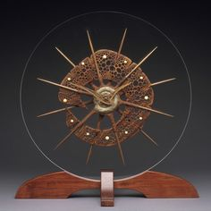 """Mantle Or Desk Clock """"Ancient Sea Form"""" A large Mantle or Desk Clock featuring a fossil ammonite at its center, carved from the South American wood Keolbra with radiating Walnut spines. The clock hangs on a round, Plexiglass back supported by a wo. Art Sculpture En Bois, Abstract Sculpture, Wood Carving Art, Wood Art, Clock Painting, Handmade Clocks, Vinyl Record Clock, Wood Clocks, Desk Clock"""