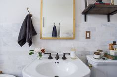 While brass details pair well with black and white, Sandie was careful not to overdo it. To keep it tasteful, she balanced the flashy brass with more subdued oil-rubbed fixtures on the sink.   Photo by Samantha Goh via Homepolish