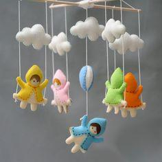 Модный детский мобиль над кроваткой новорожденногоиз четырёх фетровых подвесок с раскачивающимися на качелях девочками в ярких пальтишках, на центральной подвеске - девочка с воздушным шариком.Основанием мобиля служит карусель-перекладина из натурального деревянного массива. Яркий красоч