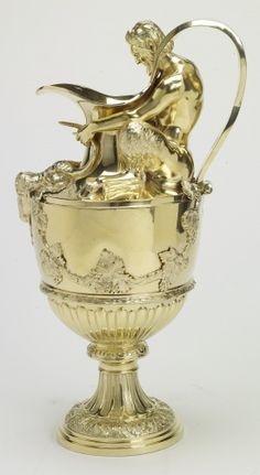 Peter Carter (active 1807) - Pair of Jugs Description: Pair of silver gilt urn-shaped jugs, the neck mounted with a cast figure of Pan, his head breaking through the entwined ribbon which forms the handle; the jug decorated with goats' masks, swags of fruiting vine, and gadrooning; on fluted stem and circular foot. Engraved with monograms and coats of arms.