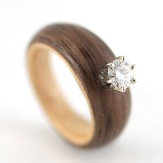 This wooden engagement ring consists of a Walnut band, Maple liner, 6-prong white gold setting and 5mm round Moissanite. This stone serves as a conflict-free alternative to diamonds.