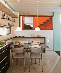 a cozinha traz piso de granilite (mistura feita na própria obra) e marcenaria de MDF, executada pelo arquiteto. A bancada de granilite preto arremata o conjunto.