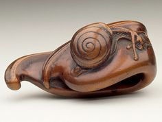 Carved wood netsuke in the shape of a bean pod and snail.18th century, Japan. LACMA (Raymond and Frances Bushell Collection)