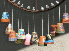 Super-fly wind chime made from an upcycled old rusty wheel and little painted terra cotta planters!