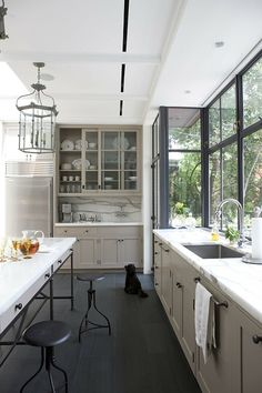 Dreamy kitchens by Robinson + Grisaru Architecture PC Luxury kitchen surrounded by windows. Marble seems to be the ultimate trend in luxurious kitchen so don't miss it out. Pastel colors and metal are always a good match. www.bocadolobo.com